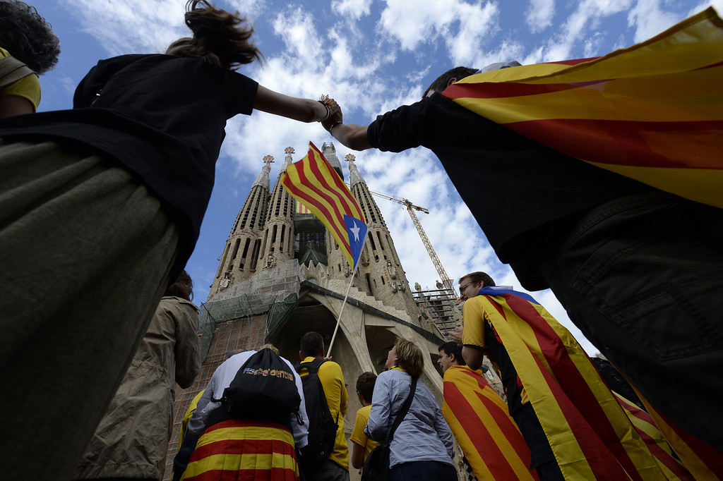 . Catalans link arms in a bid to create a 400-kilometre (250-mile) human chain, part of a campaign for independence from Spain during Catalonia National Day, or Diada, in front of the Sagrada Familia basilica in Barcelona, on September 11, 2013. Independence-seeking Catalans  marshalled their forces today to make a human link they say will stretch across 86 cities, towns and villages along the coast of the northeastern region on the Mediterranean, passing landmarks such as the Sagrada Familia basilica in Barcelona and the city\'s Camp Nou football stadium. LLUIS GENE/AFP/Getty Images