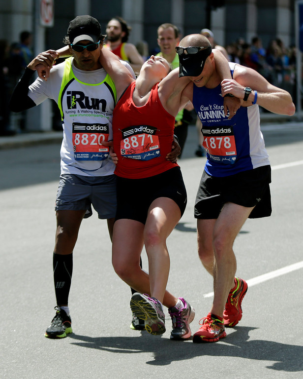 . Hugo R. Gonzalez Sr., left, of Miami, and Kyle Brumbaugh, right, of Dayton Ohio, assist Skye Taylor, of Columbus, Ohio, after she collapsed approaching the finish of the 118th Boston Marathon Monday, April 21, 2014 in Boston. (AP Photo/Robert F. Bukaty)