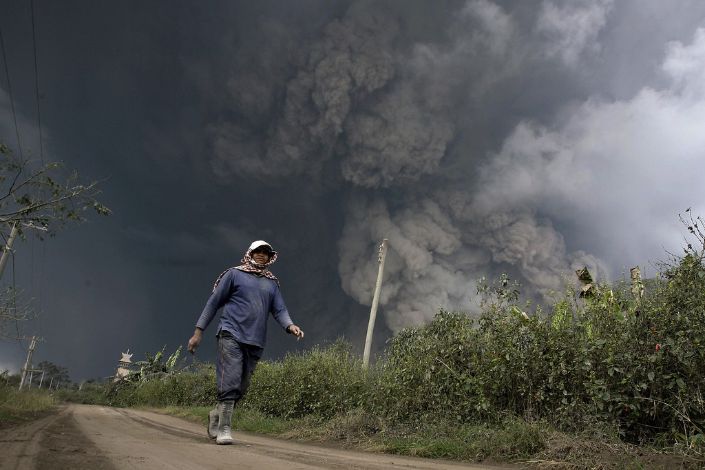 . A resident evacuates from hot volcanic ash clouds engulfing villages in Karo district during the eruption of Mount Sinabung volcano located in Indonesia\'s Sumatra island on February 1, 2014. AFP PHOTO / CHAIDEER MAHYUDDIN/AFP/Getty Images