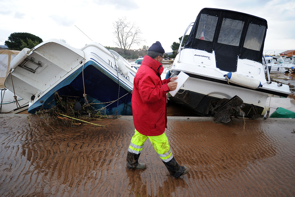 """. A man walks in front of damaged boats in the harbour of La Londe-les-Maures, southeastern France on Januray 20, 2014. River levels were receding early today in southeastern France after \""""historic\"""" floods left two people dead and more than 150 were airlifted to safety. A third man disappeared while out on his boat and 4,000 homes have been left without power after the deluge in the department of Var, they said. Local official Laurent Cayrel said one of the victims, a 73-year-old man, died in his basement, while the other was swept away in his car.  BORIS HORVAT/AFP/Getty Images"""