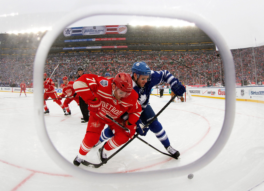 . Framed by cutout in the safety glass, Detroit Red Wings right wing Daniel Cleary (71) and Toronto Maple Leafs defenseman Cody Franson (4) battle for the puck during the third period of the Winter Classic outdoor NHL hockey game at Michigan Stadium in Ann Arbor, Mich., Wednesday, Jan. 1, 2014. (AP Photo/Paul Sancya)