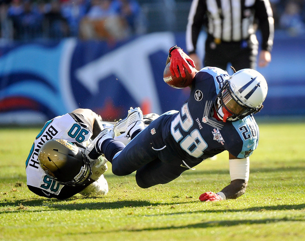 . Running back Chris Johnson #28 of the Tennessee Titans is tackled as he rushes against the Jacksonville Jaguars at LP Field on November 10, 2013 in Nashville, Tennessee.  (Photo by Frederick Breedon/Getty Images)