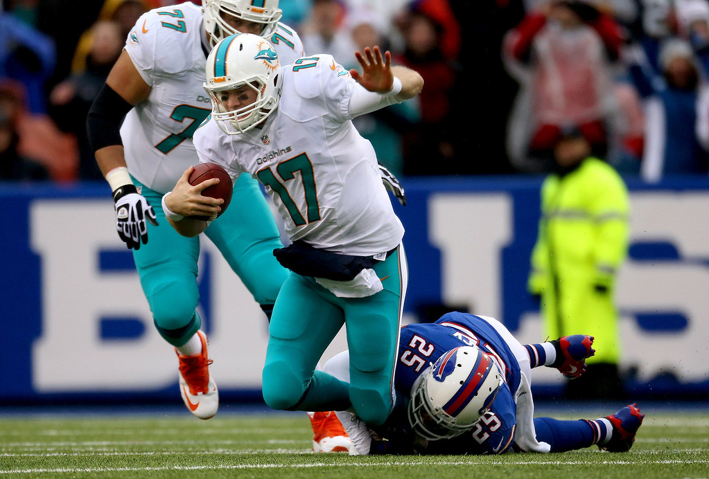 . Ryan Tannehill #17 of the Miami Dolphins is sacked during NFL game action by Da\'Norris Searcy #25 of the Buffalo Bills at Ralph Wilson Stadium on December 22, 2013 in Orchard Park, New York. (Photo by Tom Szczerbowski/Getty Images)