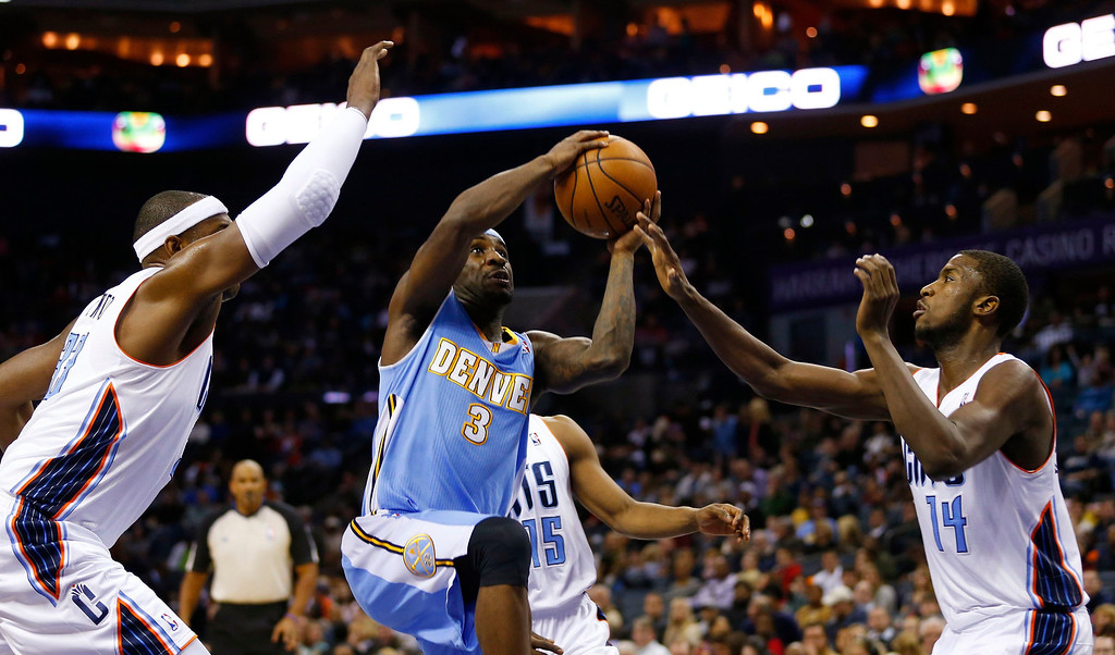 . Denver Nuggets point guard Ty Lawson (3) works to drive between Charlotte Bobcats small forward Michael Kidd-Gilchrist (14) and center Brendan Haywood (L) during the first half of their NBA basketball game in Charlotte, North Carolina February 23, 2013. REUTERS/Chris Keane