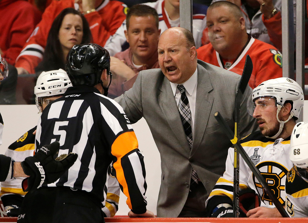 . Boston Bruins head coach Claude Julien argues with an official (5) during the second period of Game 1 in their NHL Stanley Cup Final hockey series against the Chicago Blackhawks, Wednesday, June 12, 2013, in Chicago. (AP Photo/Nam Y. Huh)