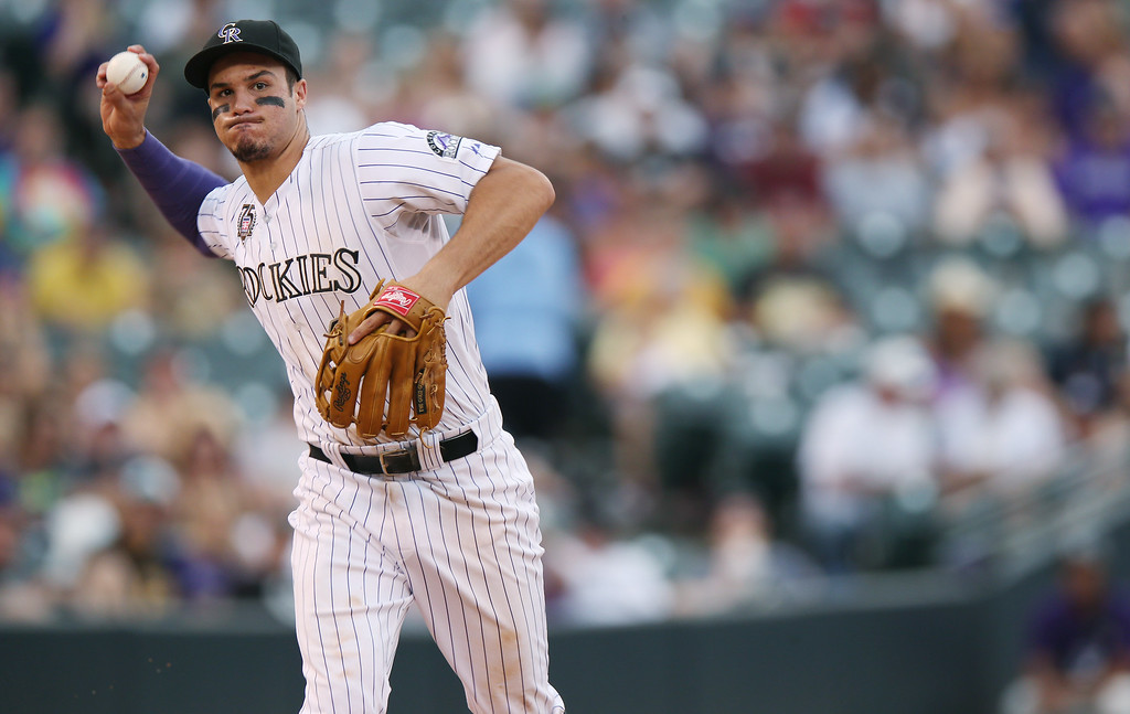 . Colorado Rockies third baseman Nolan Arenado throws to first base to put out Pittsburgh Pirates\' Andrew McCutchen in the eighth inning of the Pirates\' 7-5 victory in a baseball game in Denver, Sunday, July 27, 2014. (AP Photo/David Zalubowski)