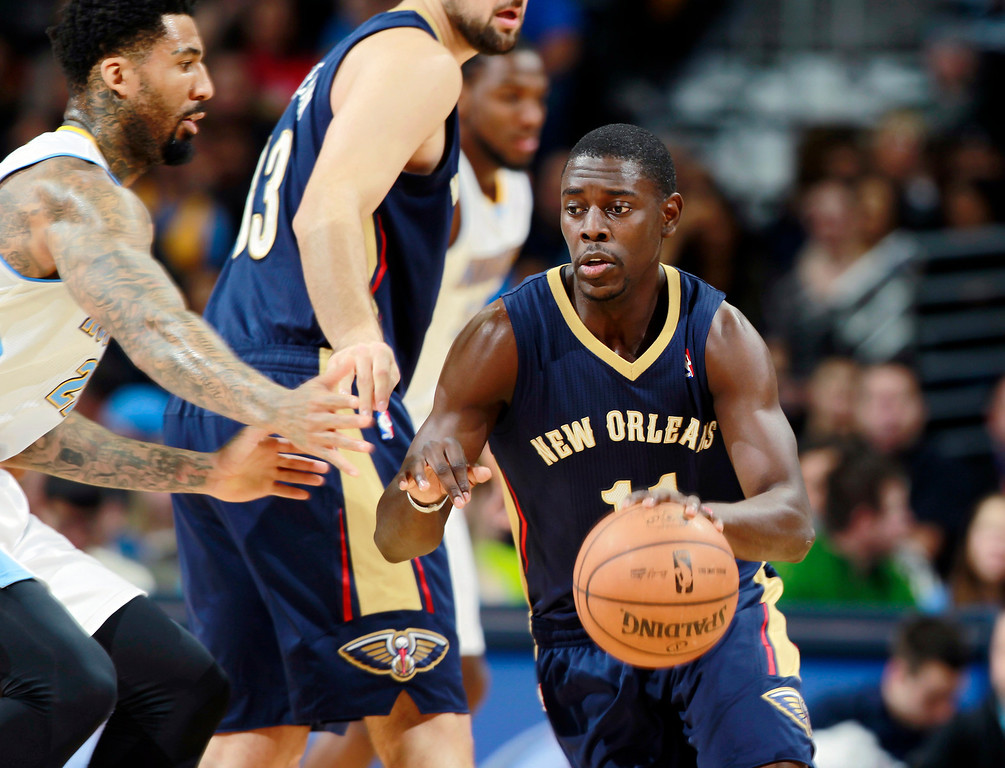 . New Orleans Pelicans guard Jrue Holiday, right, works ball inside as Denver Nuggets forward Wilson Chandler covers in the first quarter of an NBA basketball game in Denver on Sunday, Dec. 15, 2013. (AP Photo/David Zalubowski)