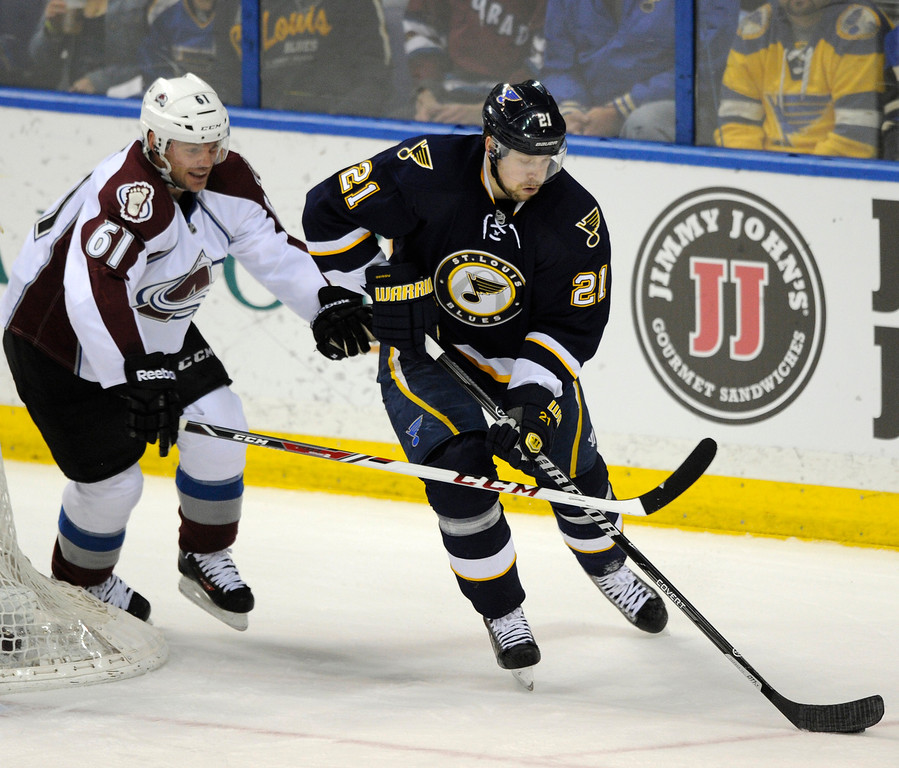 . St. Louis Blues\' Patrik Berglund (21), of Sweden, skates by Colorado Avalanche\'s Andre Benoit (61) during the second period of an NHL hockey game, Saturday, April 5, 2014, in St. Louis. (AP Photo/Bill Boyce)