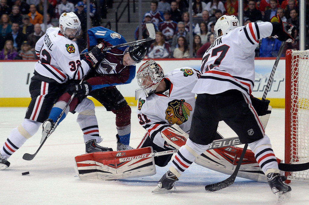 . Colorado Avalanche left wing Jamie McGinn (11) battles with Chicago Blackhawks defenseman Michal Rozsival (32) for the puck as it slides pat Chicago Blackhawks goalie Antti Raanta (31) during the third period November 19, 2013 at Pepsi Center. (Photo by John Leyba/The Denver Post)