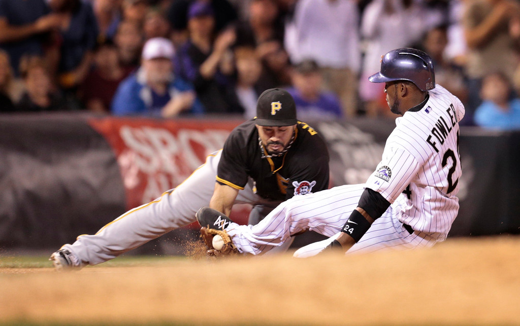 . Colorado Rockies\' Dexter Fowler, right, knocks the ball loose as he slides into PIttsburgh Pirates\' Pedro Alvarez at third base in the sixth inning of a baseball game in Denver on Saturday, Aug. 10, 2013. Fowler scored on the play. (AP Photo/Joe Mahoney)