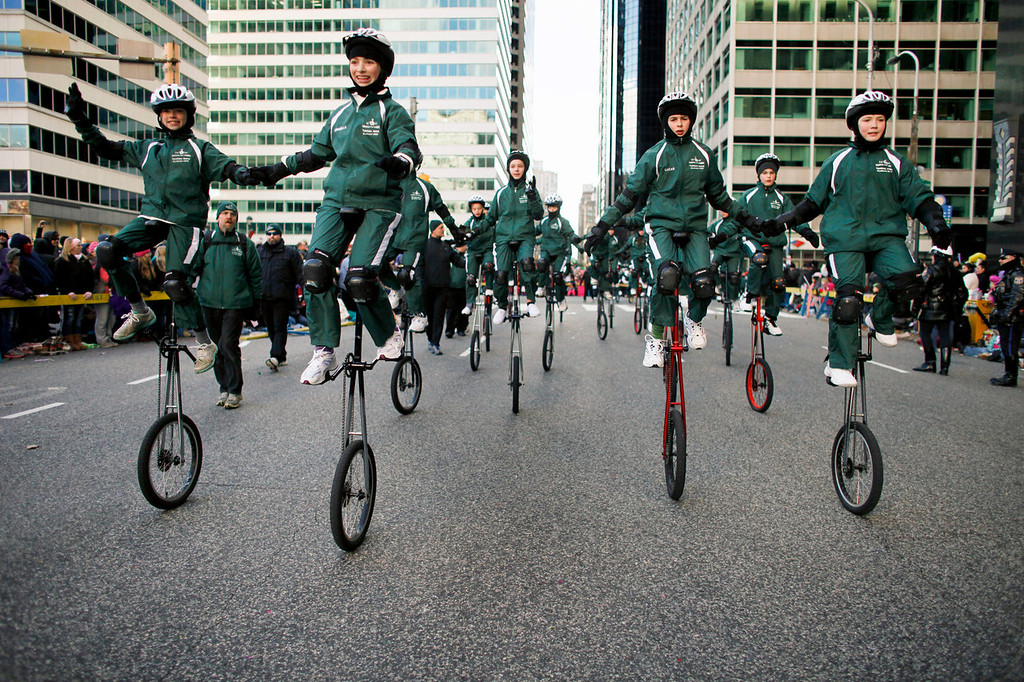 . Members of the Woodside One Wheelers participate in the 94th annual Thanksgiving day parade, Thursday Nov. 28, 2013, in Philadelphia. Officials say gusty winds limited use of balloons during parade. The National Weather Service reported winds of about 17 miles per hour gusting to 28 miles per hour at Philadelphia International Airport. (AP Photo/ Joseph Kaczmarek)