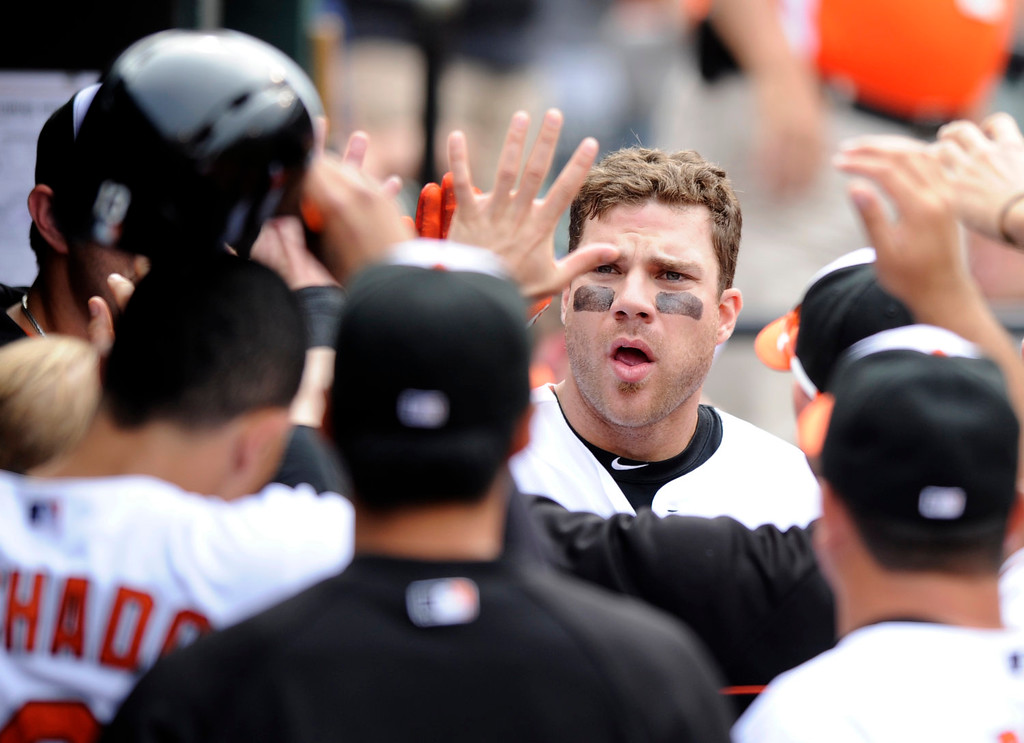 . Baltimore Orioles\' Chris Davis celebrates his two-run home run in the dugout during the eighth inning of a baseball game against the Colorado Rockies, Sunday, Aug. 18, 2013, in Baltimore. The Orioles won 7-2. (AP Photo/Nick Wass)