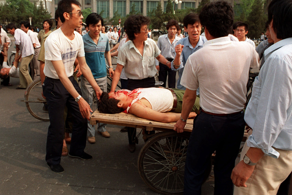 . Local residents loaded the wounded people on a rickshaw flatbed shortly after PLA soldiers opened fire on a crowd in this June 4, 1989 photo.  (AP Photo/Liu Heung Shing)