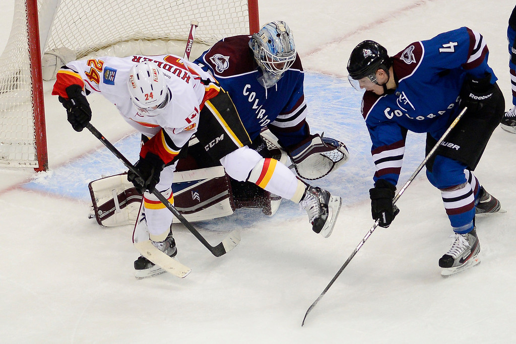 . Jiri Hudler (24) of the Calgary Flames wrangles the puck before scoring a goal as Tyson Barrie (4) of the Colorado Avalanche and Jean-Sebastien Giguere (35) of the Colorado Avalanche defend during the second period. (Photo by AAron Ontiveroz/The Denver Post)