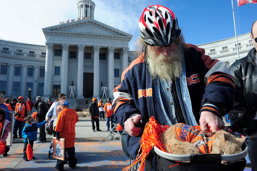 . Steve Weideman, a 43 year Denver resident, places his cat Eros into his bike basket after the conclusion of a rally to send off the Broncos, at the City and County Building in Denver, Colorado, Sunday, January 26, 2014. The noon rally brought out scores of supporters and included an appearance by Governor John Hickenlooper and Denver Mayor Michael Hancock.  (Photo By Brenden Neville / Special to The Denver Post)