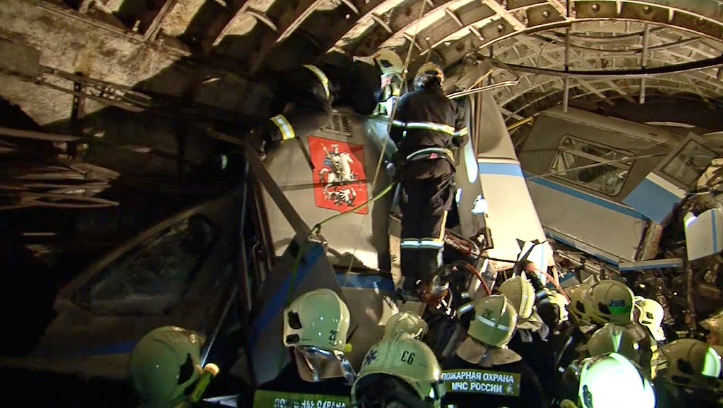 . In this frame grab provided by the Russian Ministry for Emergency Situations shows frame grab from a video showing rescue teams working inside the tunnel where several cars of the wrecked train look almost coiled, occupying the entire space of the tunnel of Moscow subway in Moscow, Russia, on Tuesday, July 15, 2014. (AP Photo/Russian Emergency Situation Ministry)