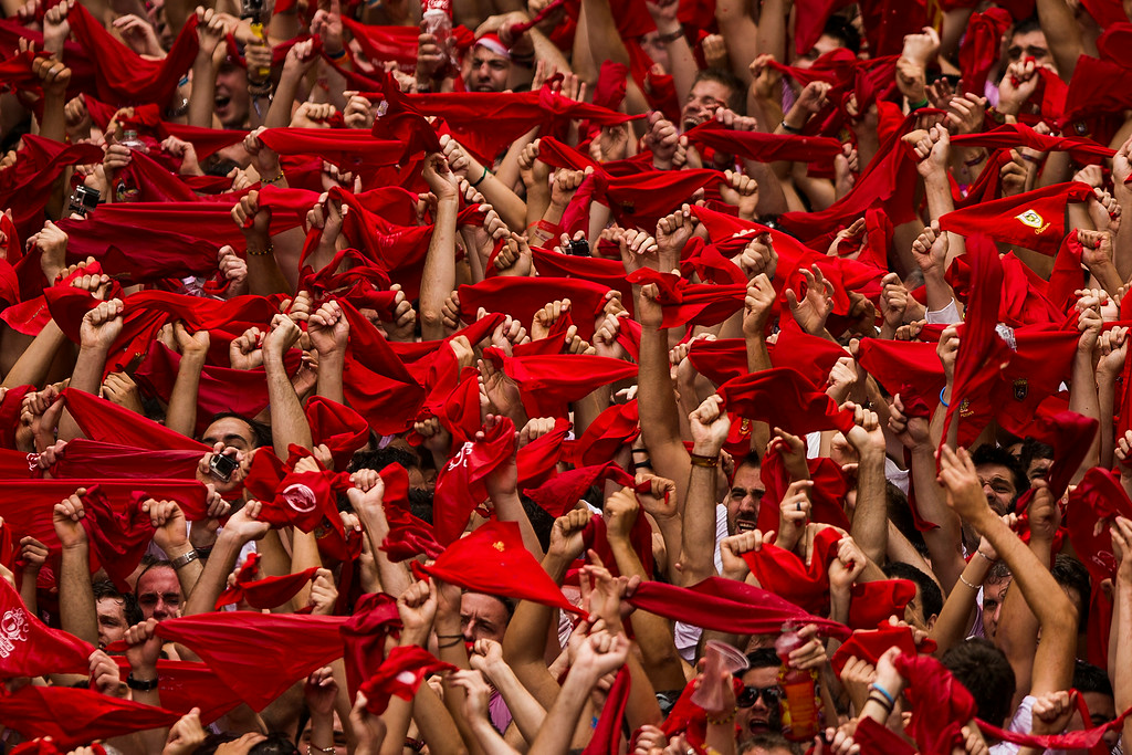 ". Revelers hold up traditional red neckties during the launch of the ""Chupinazo\"" rocket, to celebrate the official opening of the 2014 San Fermin fiestas in Pamplona, Spain, Sunday, July 6, 2014. Revelers from around the world turned out here to kick off the festival with a messy party in the Pamplona town square, one day before the first of eight days of the running of the bulls glorified by Ernest Hemingway\'s 1926 novel \""The Sun Also Rises.\"" (AP Photo/Andres Kudacki)"
