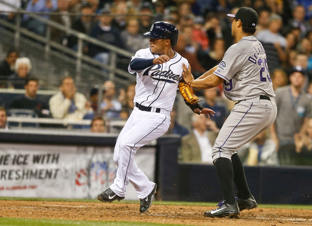 . San Diego Padres\' Alexi Amarista crosses home pate as Colorado Rockies pitcher Jorge De La Rosa awaits a throw after a pass ball by catcher Jordan Pacheco in the fifth inning of a baseball game Wednesday, April 16, 2014, in San Diego.  (AP Photo/Lenny Ignelzi)