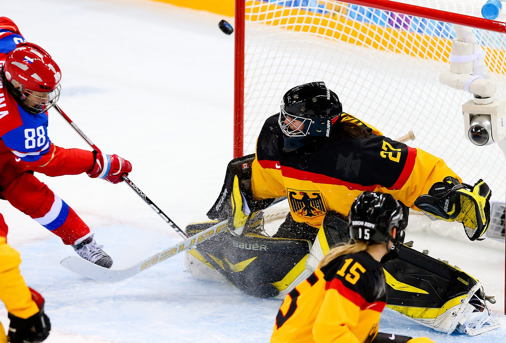 . Yekaterina Smolina (L) in action against Viona Harrer (R) the goalkeeper of Germany in the first period during the women\'s match between Russia and Germany at the Shayba Arena in the Ice Hockey tournament at the Sochi 2014 Olympic Games, Sochi, Russia, 09 February 2014.  EPA/SRDJAN SUKI