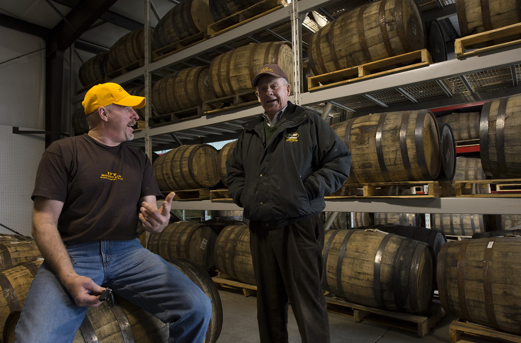 . Carlos Lovell, 85, speaks with distillery manager Mike Yearwood (R) inside the barrel aging room for sour mash whiskey at the Ivy Mountain Distillery in Mt. Airy, Georgia, USA, 26 February 2013. The Lovell family began distilling the once illegal moonshine 150 years ago in the north Georgia mountains. Carlos and his younger brother Fred learned how to make moonshine when they were teenagers, and continued making the 95 proof spirits until the early 1960s, but now have resumed their craft legally.  EPA/ERIK S. LESSER