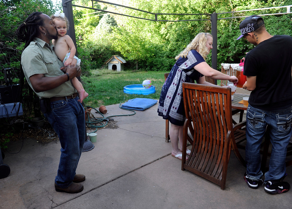 . DENVER, CO - JUNE 25: Laura and Keenon Stillman are joined by their children for a summer meal outside in the family backyard. Outside Keenon grabs a kiss from granddaughter Aspen, 1, while Laura and Aspen\'s dad, Isaiah finish setting the table. (Photo By Kathryn Scott Osler/The Denver Post)