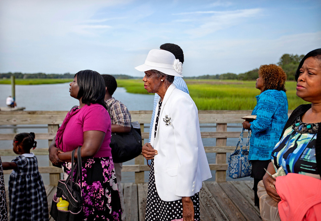 . Annie Watts, center, waits with fellow passengers to board a ferry from the mainland to attend a church service for the 129th anniversary of St. Luke Baptist Church on Sapelo Island, Ga. on Sunday, June 9, 2013. (AP Photo/David Goldman)