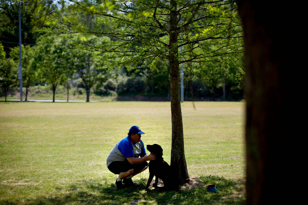 . Joseph Weaver, checks on his seeing eye dog, Moose, after a blind baseball practice in Atlanta on April 14, 2012. For the players, the game is about much more than physical activity. Faced with their own personal challenges in their daily lives, hitting and catching a ball and running full speed in total darkness teaches them they can achieve what was once thought unachievable. (AP Photo/David Goldman)