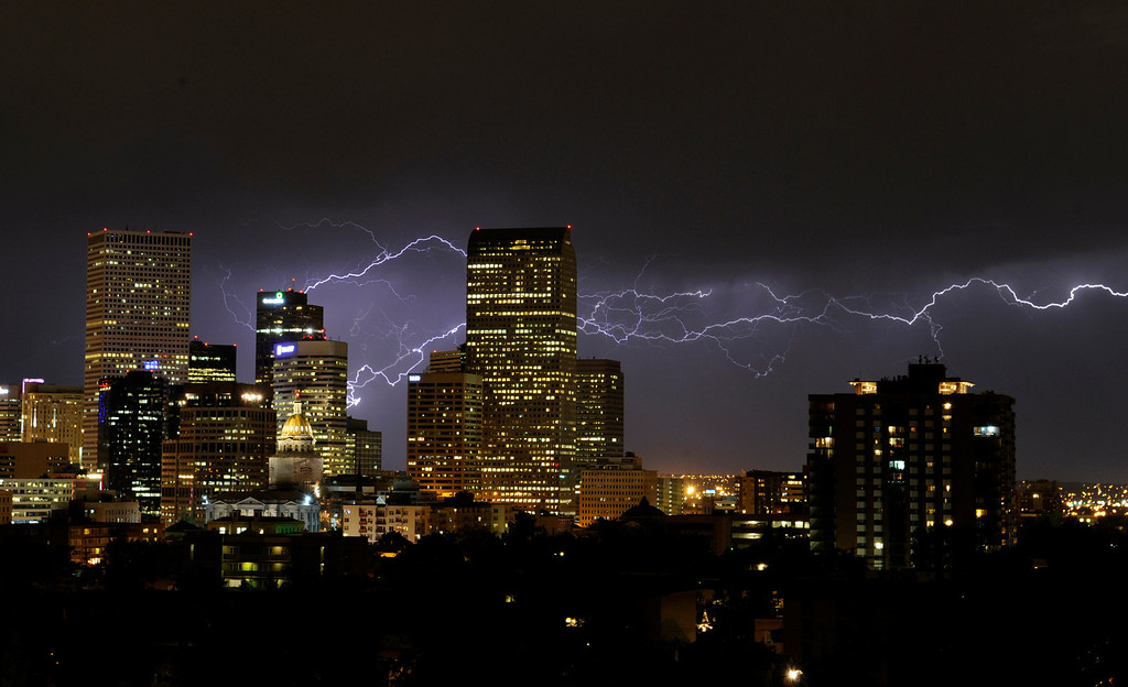 . An electrical storm sent a bolt of lightning racing across the sky above downtown Denver on July 24, 2012.  Karl Gehring/The Denver Post