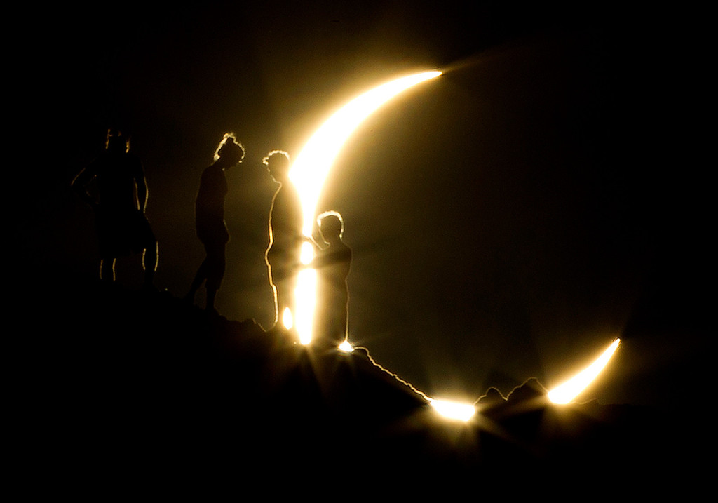 . In this May 20, 2012 file photo, hikers watch an annular eclipse from Papago Park in Phoenix. The annular eclipse, in which the moon passes in front of the sun leaving only a golden ring around its edges, was visible to wide areas across China, Japan and elsewhere in the region before moving across the Pacific to be seen in parts of the western United States. (AP Photo/The Arizona Republic, Michael Chow, File)