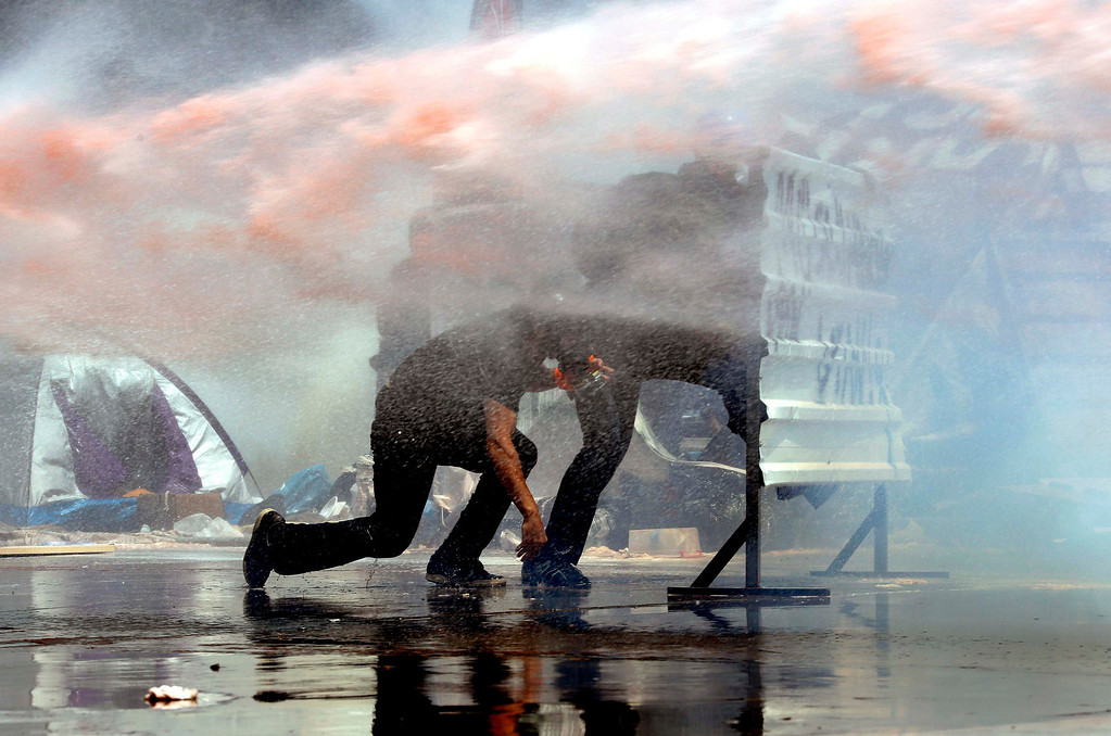 . Protesters take cover behind a barricade as a police water cannon sprays high pressure water during clashes in Istanbul\'s Gezi Park, next to Taksim square June 11, 2013.  REUTERS/Yannis Behrakis