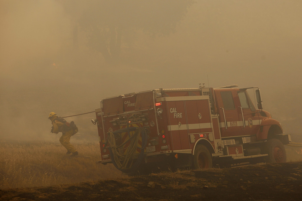 . A firefighter pulls a hose into position to battle the Cocos fire on May 15, 2014 in San Marcos, California. Fire agencies throughout the state are scrambling to prepare for what is expected to be a dangerous year of wildfires in this third year of extreme drought in California.   (Photo by David McNew/Getty Images)