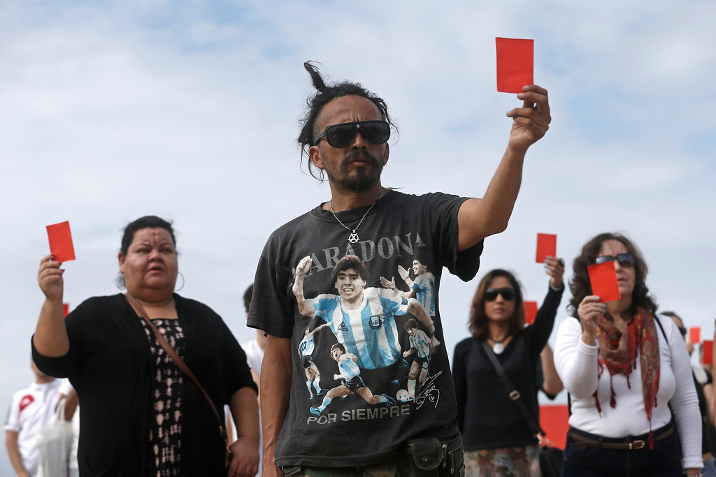 . A demonstrator wearing a T-shirt with a photo of Argentina\'s former soccer player Maradona holds up a red card at a protest against the public money spent on the World Cup in the Copacabana beach in Rio de Janeiro, Brazil, Saturday, June 21, 2014. Organized by Rio de Paz, protesters say the money spent on the international soccer tournament should have been used to improve schools, health care and security in shantytowns. (AP Photo/Silvia Izquierdo)