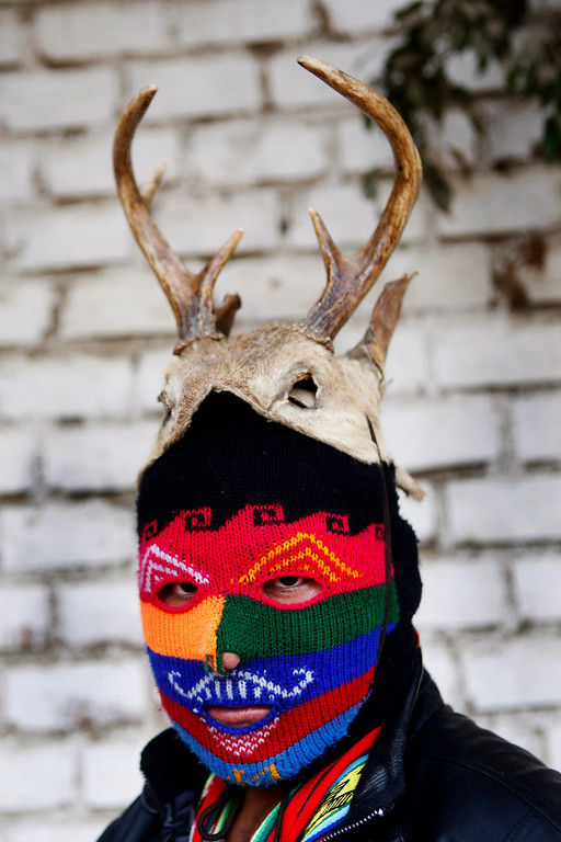 """. Masked fighter Daniel Flores poses for a portrait before taking part in a Takanakuy ritual fight in Lima, Peru. The fighters dress up in costumes of Andean folklore figures, with the ski masks an integral part of the costume. Among the characters: \""""El Negro,\"""" representative of black slaves; \""""El Majeno,\"""" reminiscent of liquor salesmen from a region called Majes; and \""""El Gallo,\"""" the rooster. (AP Photo/Karel Navarro)"""