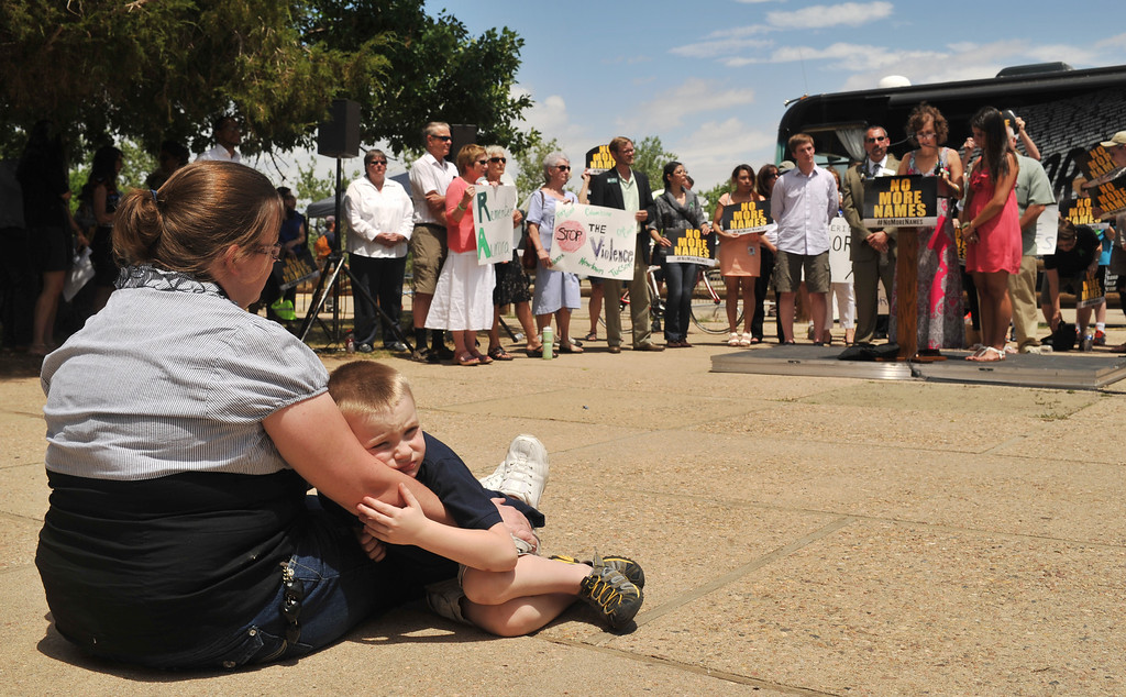 . AURORA, CO. - July 19: Rose Richards of Golden holds her son Jake, 4, during the remembrance event for the one year anniversary of the Aurora theater shooting at Smokey Hill Shelter in Cherry Creek State Park. Aurora, Colorado. July 19, 2013. Two groups met at the park to mark the first anniversary of the Aurora movie theater massacre � one to remember those killed by guns, and the other rally to support the Second Amendment. (Photo By Hyoung Chang/The Denver Post)