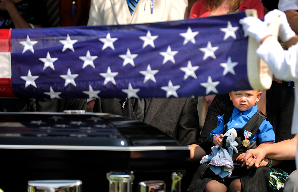 . Two-year-old Maximus Blunk watches as the flag is folded on his father\'s casket, Friday, August 03, 2012, during a full military funeral for Jonathan Blunk at Mountain View Mortuary in Reno, Nevada.