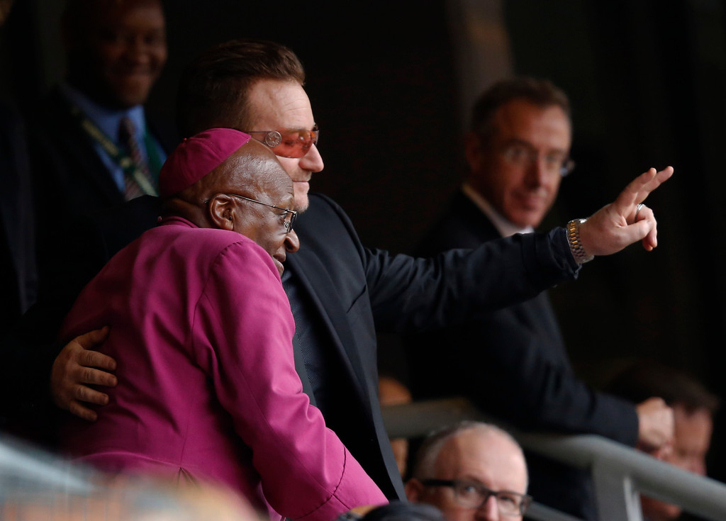 . Retired Anglican Archbishop Desmond Tutu and musician Bono wave to mourners during the memorial service for former South African president Nelson Mandela at the FNB Stadium in Soweto near Johannesburg, Tuesday, Dec. 10, 2013. (AP Photo/Ben Curtis)