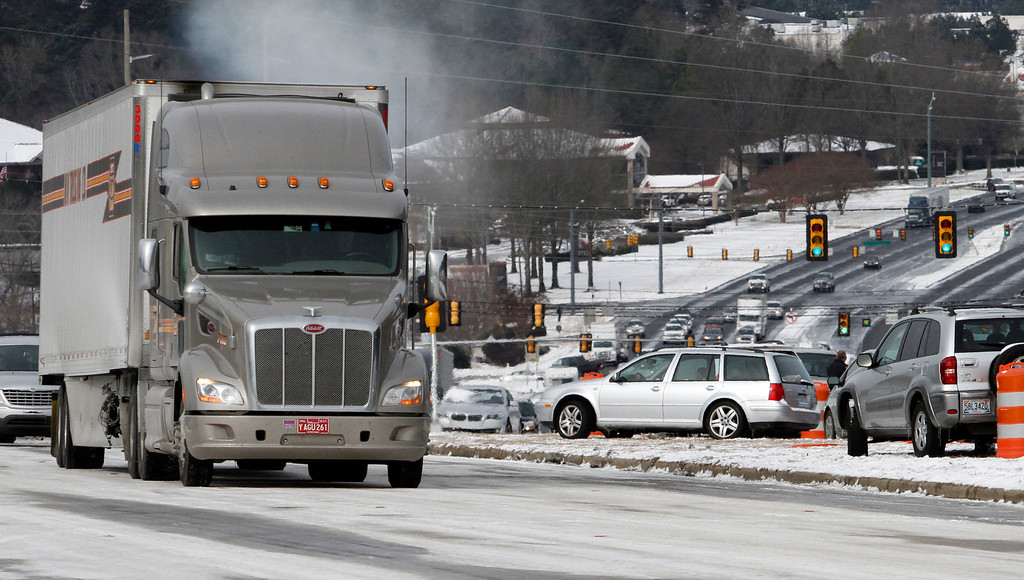 . Icy conditions and abandoned  vehicles has traffic at a stand still along Highway 280 on Wednesday, Jan. 29, 2014, in Inverness, Ala. A Winter storm caught much of Alabama off guard and stranded thousands of people at work, schools and on roadways. (AP Photo/Butch Dill)