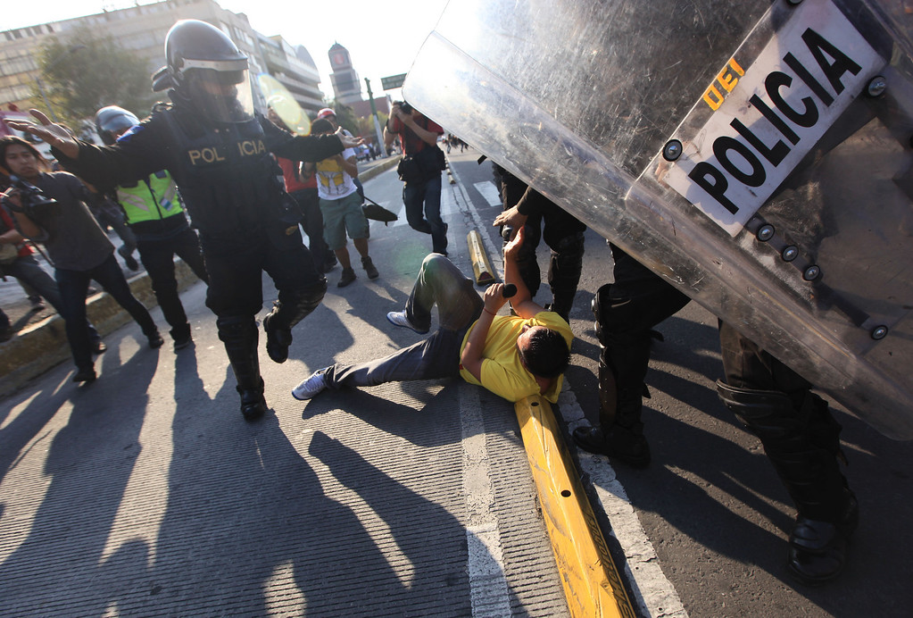 . A man on the ground holding a microphone who yelled that he is a journalist is kicked by police during a march by protesters on the anniversary of the Tlatelolco massacre in Mexico City, Wednesday, Oct. 2, 2013.  The officers left the scene after other members of the media intervened on the man\'s behalf. Mexico commemorated the 45th anniversary of the massacre of students holding an anti-government protest days before the 1968 Summer Olympics celebrations in Mexico City. (AP Photo/Eduardo Verdugo)