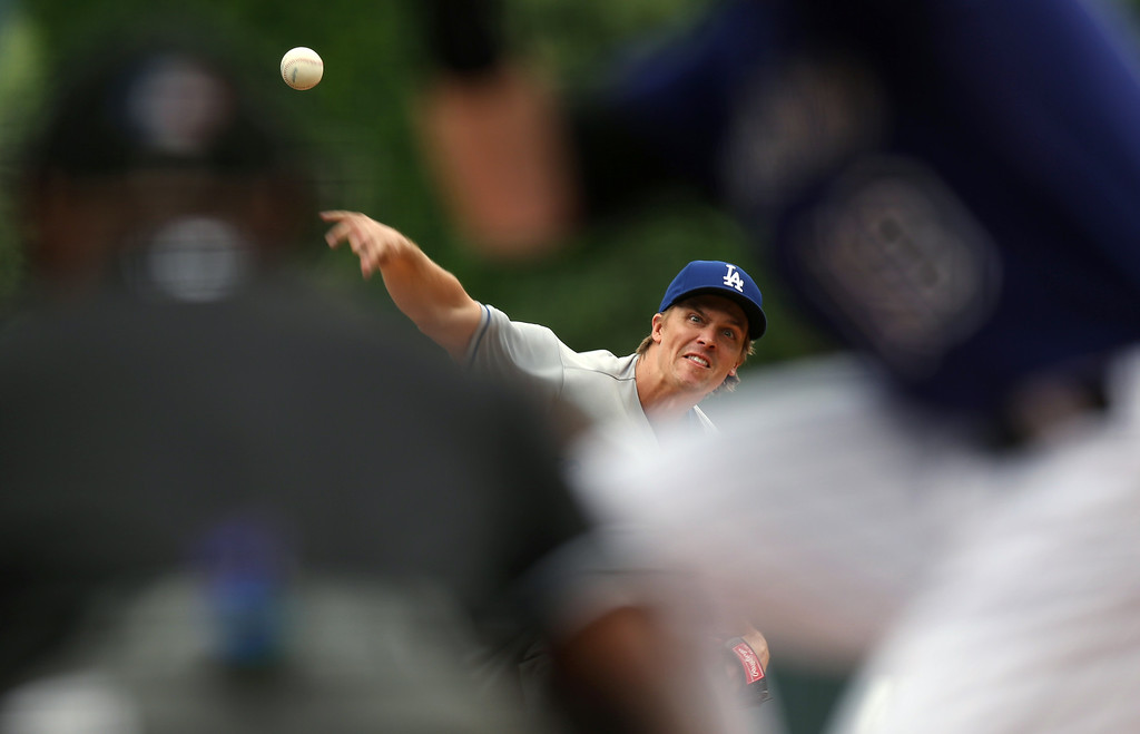 . Los Angeles Dodgers starting pitcher Zack Greinke, back, works against the Colorado Rockies in the first inning of a baseball game in Denver on Saturday, June 7, 2014. (AP Photo/David Zalubowski)