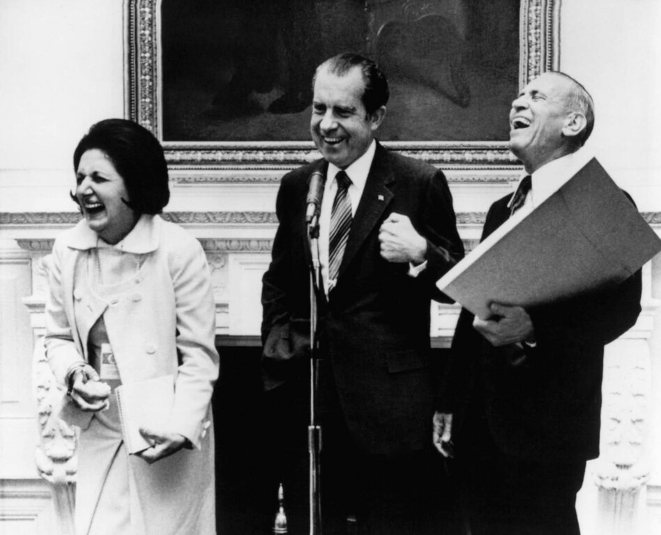 . President Richard Nixon shares a laugh with Douglas Cornell, White House reporter for the Associated Press, right, and Helen Thomas, UPI  White House reporter at an impromptu reception at night on Sept. 30, 1971 in Washington. (AP Photo)