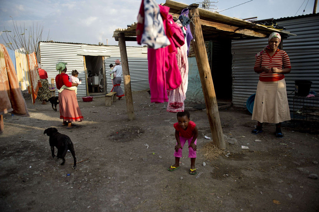 . Women and children gather between shacks on July 9, 2013 in the Nkaneng shantytown next to the platinum mine, run by British company Lonmin, in Marikana. On August 16, 2012, police at the Marikana mine open fire on striking workers, killing 34 and injuring 78, during a strike was for better wages and living conditions. Miners still live in dire conditions despite a small wage increase.  ODD ANDERSEN/AFP/Getty Images