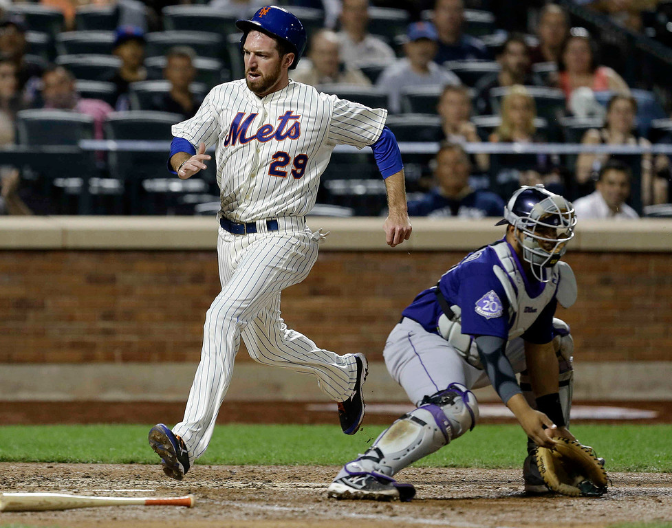 . New York Mets\' Ike Davis runs past Colorado Rockies catcher Wilin Rosario to score on a single by John Buck during the fourth inning of a baseball game Wednesday, Aug. 7, 2013, in New York. (AP Photo/Frank Franklin II)