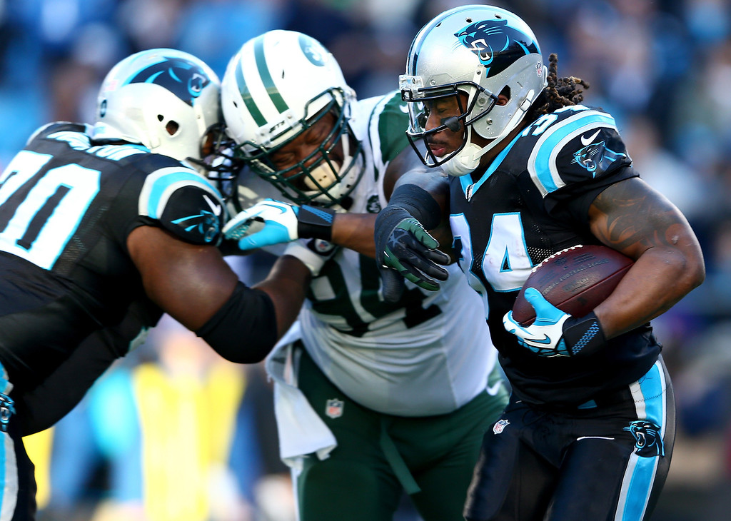 . Damon Harrison #94 of the New York Jets tries to tackle DeAngelo Williams #34 of the Carolina Panthers during their game at Bank of America Stadium on December 15, 2013 in Charlotte, North Carolina.  (Photo by Streeter Lecka/Getty Images)