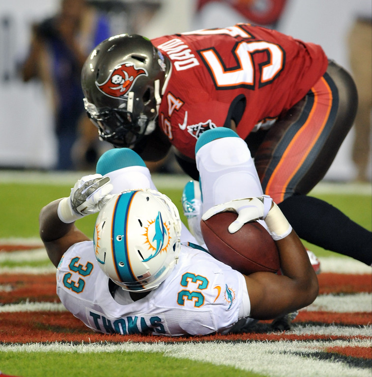 . Linebacker Lavonte David #54 of the Tampa Bay Buccaneers tackles running back Daniel Thomas #33 of the Miami Dolphins for a safety November 11, 2013 at Raymond James Stadium in Tampa, Florida. Tampa won 22 - 19. (Photo by Al Messerschmidt/Getty Images)