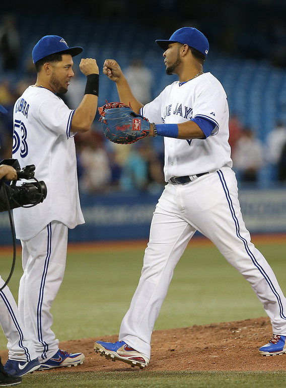. Edwin Encarnacion #10 of the Toronto Blue Jays celebrates with Melky Cabrera #53 after defeating the Colorado Rockies during MLB game action on June 18, 2013 at Rogers Centre in Toronto, Ontario, Canada. (Photo by Tom Szczerbowski/Getty Images)