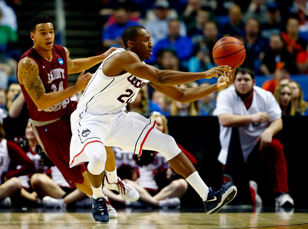 . BUFFALO, NY - MARCH 20:  Lasan Kromah #20 of the Connecticut Huskies controls the ball as Chris Wilson #24 of the Saint Joseph\'s Hawks defends during the second round of the 2014 NCAA Men\'s Basketball Tournament at the First Niagara Center on March 20, 2014 in Buffalo, New York.  (Photo by Jared Wickerham/Getty Images)