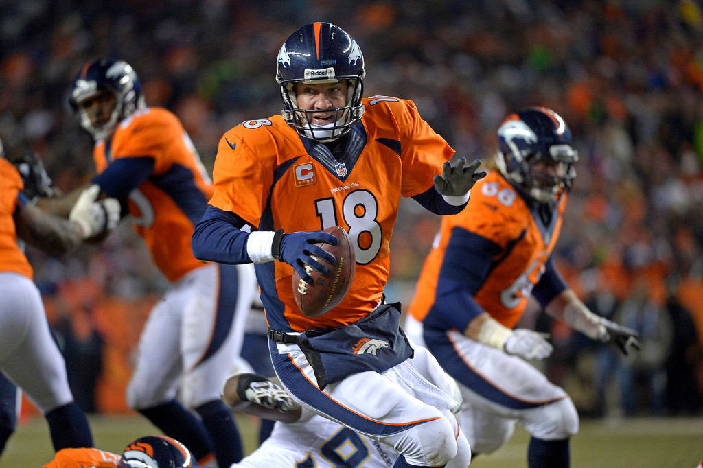 . Denver Broncos quarterback Peyton Manning (18) scrambling during the second quarter. The Denver Broncos vs. the San Diego Chargers at Sports Authority Field at Mile High in Denver on December 12, 2013. (Photo by Joe Amon/The Denver Post)