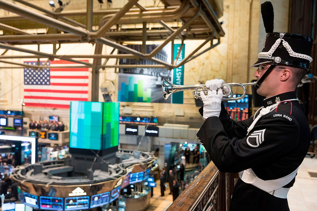 . Staff Sgt. Bryan McKinney, of the U.S. Military Academy Band at West Point , plays Taps on a balcony of the New York Stock Exchange, in honor of Veteran\'s Day, Monday, Nov. 11, 2013. (AP Photo/Ben Hider, NYSE)
