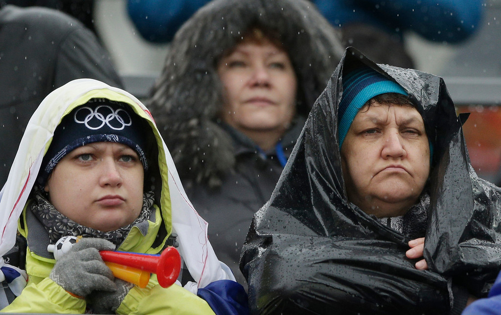 . Spectators wear rain gear as they watch the Nordic combined individual Gundersen large hill competition at the 2014 Winter Olympics, Tuesday, Feb. 18, 2014, in Krasnaya Polyana, Russia. (AP Photo/Matthias Schrader)