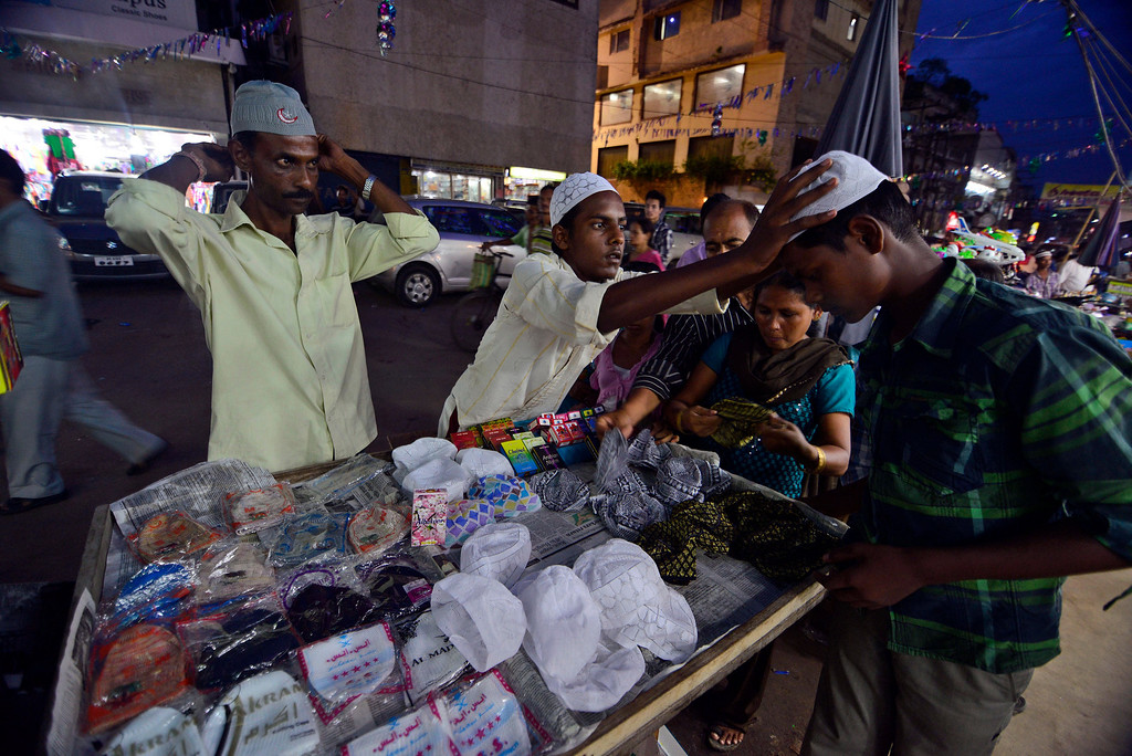 . Indian Muslims shop for caps ahead of Eid al-Fitr in Gauhati, India, Thursday, Aug. 8, 2013. Eid al-Fitr marks the end of the holy month of Ramadan, during which Muslims all over the world fast from sunrise to sunset. (AP Photo/Anupam Nath)
